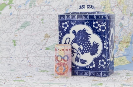 Chinas yuan currency placed on a map in front of an antique Chinese porcelain serves to symbolize Chinas market influence on the world economy. 版權商用圖片