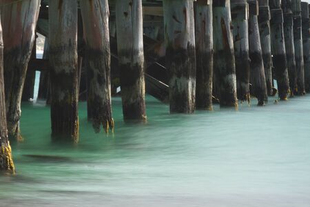 Beautiful green of a silky, low tide sweeps beneath the timbers of an ocean pier.  Location is Vivonne Bay, Kangaroo Island, Australia. Stock Photo