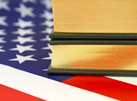 Close up of books with gold edge pages placed on an American flag Stock Photo