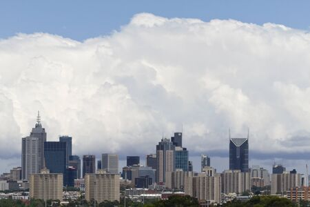 Cityscape of Melbourne, Australia; skyline of city with billowing white clouds and blue skys above and beyond. Location is province of Victoria, Melbourne, Australia;