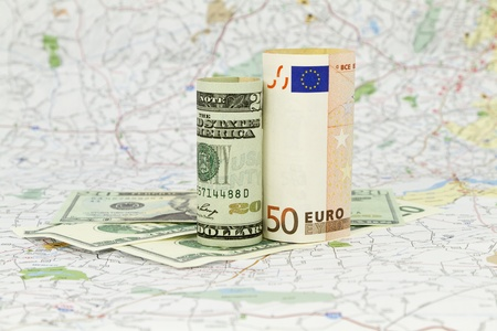 Two currencies, dollar and euro, placed on a map indicate the shared nature and dependencies within a global economys market and financial system.  Stock Photo