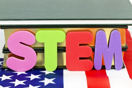skill: Popular designation of STEM education (Science, Technology, Engineering, and Mathematics) references life and career-ready skills for 21st century success. Letters S,T, E, M, placed before books and on American flag.