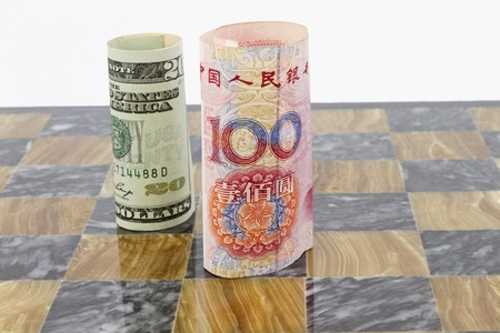 opponents: Dollar and yuan currency stand on marble chess board; opponents in financial game; political or policy conflict in game of life;  Stock Photo
