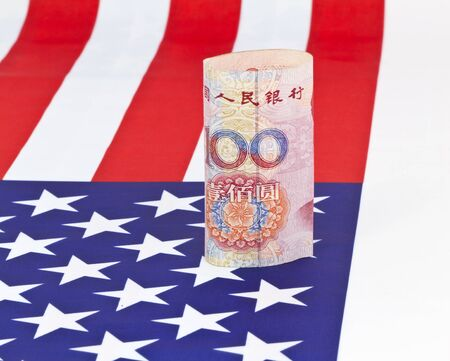 Chinas yuan currency placed on an American flag reflects concept of Asian investments made in America as well as Asian and American business partnerships;