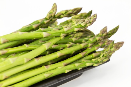 Fresh asparagus spears, close up on long, dark dish
