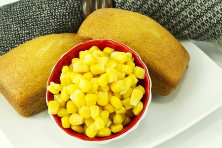 corn meal: Black and gray woven napkin placed with freshly baked corn bread sits with the key ingredient of corn meal -- golden, seasonal corn.