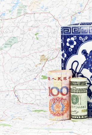 Two global currencies, yuan and dollar from the USA and China, placed together on map reflect global travel, business and leisure.