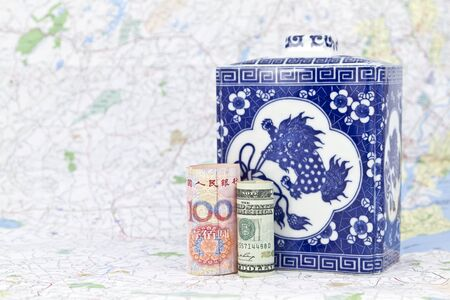 initiatives: Two global currencies, yuan and dollar from the USA and China, placed together on map in front of antique, household jar are reflective of global commerce and shared leadership initiatives.