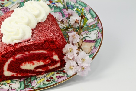 Red velvet cake roll with cream cheese frosting,  inside and on top, is placed on feminine platter with pink flowers; Stock Photo - 13223036