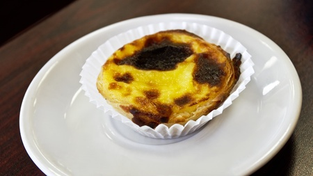 Custard pastry, traditional Portuguese pasteis de nata on a white plate placed on wood grain table   Egg custard has a creme brulee-like consistency and is in a flakey, puff pastry    Stock Photo