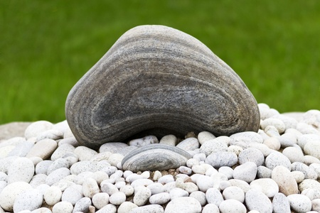 kinship: Two natural rock elements, one large and one small, of Zen garden are placed to capture similarity and harmony; layers in rock are visible;
