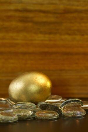 Oro huevo brilla en las piedras de cristal delante del fondo de madera del grano, imagen vertical con copia espacio en la parte superior; Foto de archivo - 13636982