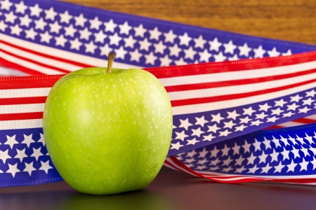 suggests: Green apple placed on  stars and stripes ribbon with USA flag motif; apple suggests school, education, environment, as well as health, food, obesity, fitness issues that impact the nation.