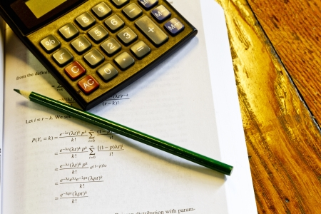 Calculator, pencil, and mathematics book on oak table suggest budget work or homework. Stock Photo - 13880240