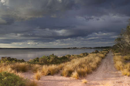 Sandy road along bay with cloud-filled sky as storm passes and sunlight breaks through.  Stokes Bay, Kangaroo Island, South Australia. photo