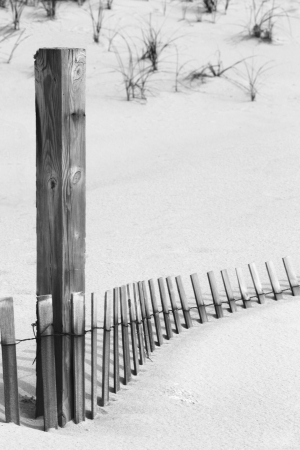 Weathered wooden post and partially buried fencing in sand in black and white, monochrome image.  Location is New Jersey Shore, on the sand dunes of Island Beach State Park.  Stock Photo