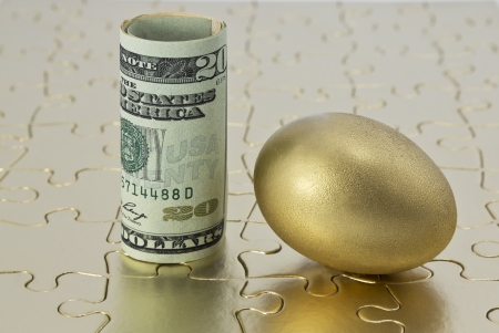 Gold egg and rolled, dollar currency placed on shiny golden puzzle in reflection of complex investment and savings strategies necessary for successful solutions.