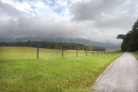 Fence and road of Cades Cove  in Great Smoky Mountains National Park.  Journey evoked by gravel, Appalachian road.