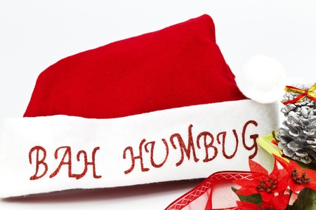 bah: Red and white Santa Claus hat placed with silver pine cones, ribbons, and poinsetta flowers on white background