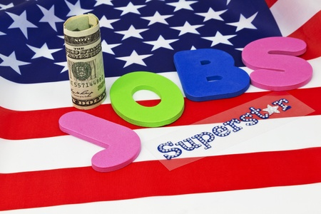 emphasizes: Letters spelling JOBS placed on American flag with currency and Superstar in glitter letters emphasizes critical nature of employment in today Stock Photo