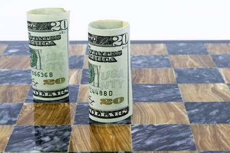 monetary policy: Game board of brown and black marble has two, rolled American dollars, standing upright.