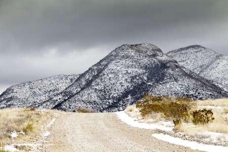 Snow touches rugged Dragoon Mountains, south of Tucson, AZ; metaphor of path and journey seen in rising road.