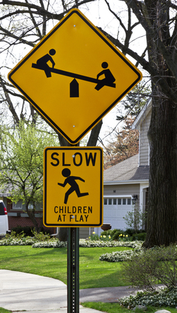 cautions: Children at Play road sign in neighborhood cautions to drive slowly; depicts children on see saw and running child   Location is Northbrook, Illinois, a suburb of Chicago in the United States