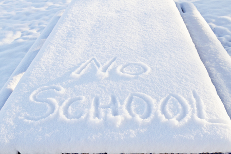 No School carefully printed in fresh snow indicates winter weather has closed local schools.
