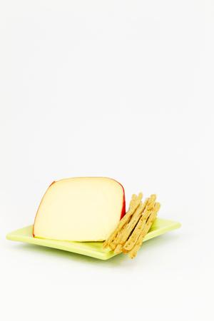 breadsticks: Rebanada de queso amarillo con c�scara roja colocada con palitos de pan en verde, placa cuadrada sobre fondo blanco, la imagen vertical, con grandes �reas de espacio de la copia