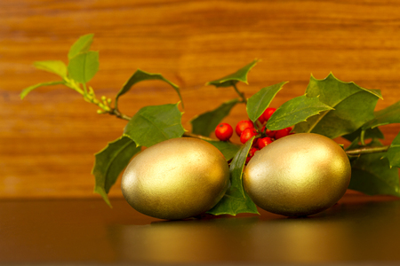 gleam: Two gold nest eggs with festive green holly sprigs and red berries placed on wood grain background;