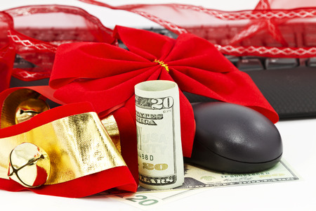 Red ribbon, American currency, and Christmas bells encirle keyboard and mouse. photo