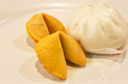 stoneware: One Chinese steamed bun next to two fortune cookies on a rustic,  beige stoneware plate.