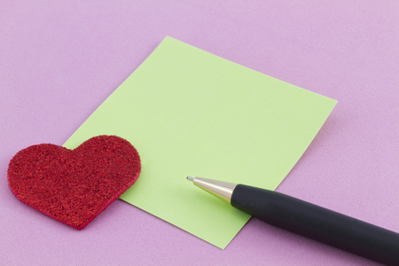 Sparkling red heart next to green note square with black pen\ on pink background. Copy space available.