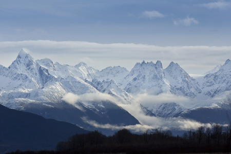Majesty of Chilkat Mountains seen from the Haines Highway in Alaska.  The raw, towering Chilkat Mountains, part of the Coast Range of Southeast Alaska, are dramatic scenery along the Inside Passage, a route with major tourist attractions.  Chilkat Mountai Stock Photo