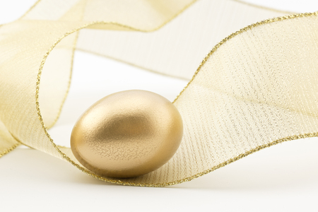 Gold nest egg placed in swirl of golden metallic ribbon creates sense of movement, excitement, and success.