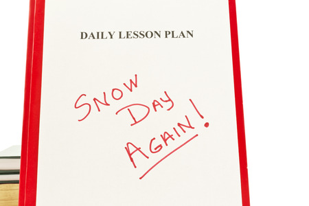 Daily Lesson Plan sheet with handwritten SNOW DAY AGAIN in red letters with school books in background Stok Fotoğraf