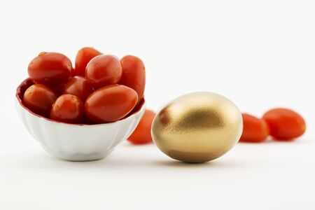 Cherry tomatoes placed with gold egg on white background with copy space available.  Metaphors suggest fresh agriculture, local produce, farm industry, restaurant business, ogranic foods, are successful investments.  Healthy diet and nutrition pay off. Stock Photo