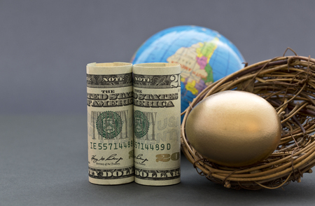 global retirement: American dollars and gold nest egg with globe in sophisticated, gray background.  Success suggested by global investment and worldwide financial business. Selective focus on key, front metaphors.
