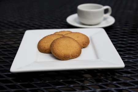 Selective focus on butter cookies on white plate with espresso visible in shallow depth of field.  Snack items on black metal mesh patio table.