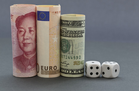 investment risks: Financial investment risks reflected in dice next to dollar, euro, and yuan money on gray and blue hued background.  Three currencies build concept of global marketplace and  shared gambles. Stock Photo