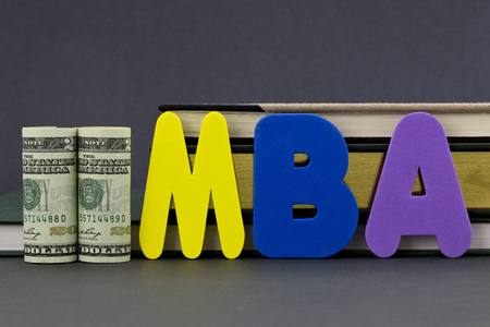 Graduate degree MBA letters with dollar currency in front of books on gray background.  Advance degree is a education business investment in critical skills. Stock Photo