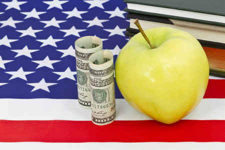 emphasis: Symbolic apple representative of education placed with American currency, national flag, and books reflects emphasis on important financial support for education. Stock Photo