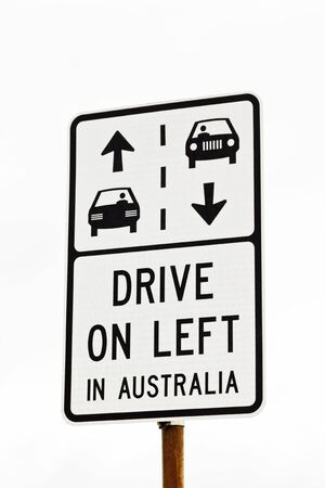 traffic regulation: White and black sign indicating Drive on Left in Australia traffic regulation, an important distinction to American travelers and tourists. Stock Photo