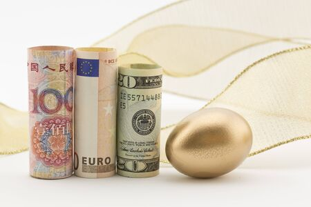 global currencies: Three major currencies with gold egg and flourish of ribbon reflect savvy business investments, savings, and collaboration on a global scale.