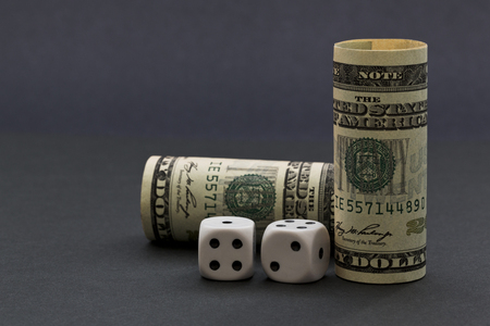 Sophisticated gray background image with United States dollars and black and white dice reflects risk in financial environment with opportunities for success.