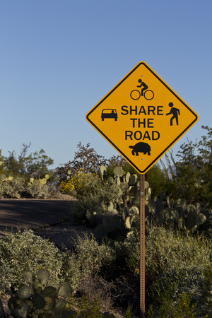 bicyclists: In bicycle friendly Saguaro National Park, a Share the Road sign warns that roadway must be shared by cars, bicyclists, walkers, and desert wildlife, including slow moving tortoises.  Location is Tucson, Arizona.