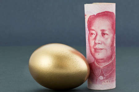 soothing: Chinese currency, Asian yuan, stands upright next to gold nest egg on soothing dark background reflects Pacific Rim strength and success in business and investment.