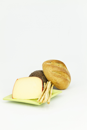 Vertical image with dark and light breads placed with gouda cheese and breadsticks on white background.