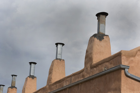architectural details: Row of chimneys on adobe building in Old Town district of Albuquerque, New Mexico.  Copy space in sky above architectural details. Stock Photo