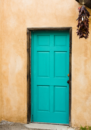 Old Pueblo Spanish style building with adobe walls enhanced by blue door with hanging red peppers.  Location is Old Town district in Albuquerque, New Mexico, in Americas Southwest region.  Vertical image with copy space. Stock Photo